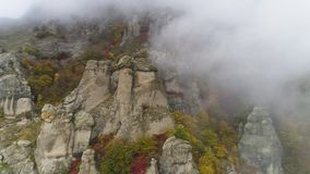 Top view on relief of rocks autumn in fog. Shot. View of rock formations of mountain with colored dry grass and shrubs