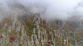 Top view on relief of rocks autumn in fog. Shot. View of rock formations of mountain with colored dry grass and shrubs. On fog background royalty free stock photos