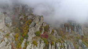 Top view on relief of rocks autumn in fog. Shot. View of rock formations of mountain with colored dry grass and shrubs. On fog background royalty free stock images