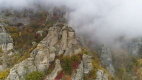 Top view on relief of rocks autumn in fog. Shot. View of rock formations of mountain with colored dry grass and shrubs. On fog background stock photography
