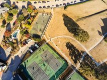 Top view residential tennis courts with players at autumn morning in North Texas, America. Aerial drone view park side residential neighborhood with community stock images