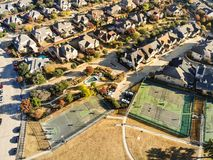 Top view residential tennis courts with players at autumn morning in North Texas, America. Aerial drone view park side residential neighborhood with community royalty free stock image