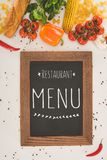 Top view of restaurant menu in wooden frame and fresh vegetables. On white Royalty Free Stock Image