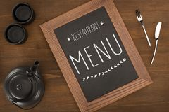 Top view of restaurant menu in wooden frame, tea set and cutlery. On wooden table stock photos