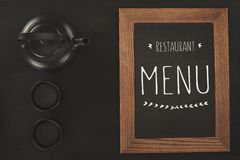 Top view of restaurant menu in wooden frame and tea set. On black royalty free stock image