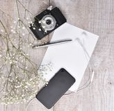Top view of retro camera, phone, earphones and notebook on a li Royalty Free Stock Images