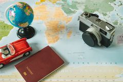 Top view. retro camera, world, car and passport placed on top of. Top view. retro camera, world, toy car and passport placed on top of color world map are Royalty Free Stock Images