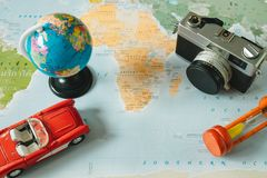 Top view. retro camera, world, car, clock and passport placed on. Top view. retro camera, world, toy car, sand clock and passport placed on top of color world Stock Images