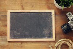Top view and retro filtered image of blank old chalkboard, nautical rope and camera. travel and adventure concept Stock Photo