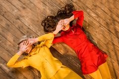 Top view of retro styled girls in colorful dresses lying on floor and covering eyes with hands at home royalty free stock images
