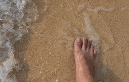 Top view and right foot, man on sand and waves sea in summer.  Royalty Free Stock Photo