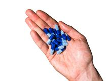Top view of right, white, hand holding blue pills on white background stock photo