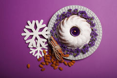 Top view of ring cake with an alight candle, cinnamon, almond and white snowflakes on a bright violet background. Top view of a plate with a round cake covered Royalty Free Stock Images