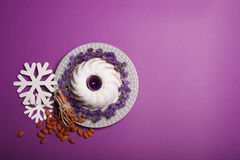 Top view of ring cake with an a light candle, cinnamon, almond and white snowflakes on a bright violet background. Top view of a plate with a round cake covered Royalty Free Stock Photography
