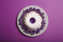 Top view of a ring cake sprinkled with powdered sugar, with a violet candle in a center on a bright violet background. Stock Images