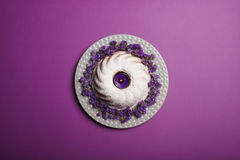 Top view of a ring cake sprinkled with powdered sugar, with a violet candle in a center on a bright violet background. Royalty Free Stock Photo
