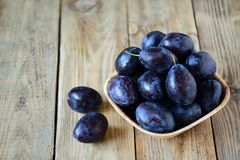 Top view. Ripe blue plums with water drops in a wooden bowl on a. Wooden background. Summer seasonal fruit concept. Rustic style royalty free stock photo