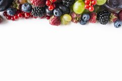 Top view. Ripe blueberries, blackberries, red currants, grapes, raspberries and plums. Various fresh summer berries on white background. Berries and fruits Stock Images
