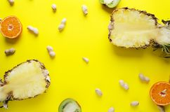 Top view of ripe fruits, unpeeled peanuts on bright yellow surface. stock images