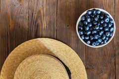 Summer close-up of blueberries and straw hat on vintage wooden background. Top view of ripe and juicy fresh picked bilberries in white bowl. Pretty beautiful Stock Image