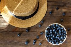 Summer close-up of blueberries and straw hat on vintage wooden background. Top view of ripe and juicy fresh picked bilberries in white bowl. Pretty beautiful Royalty Free Stock Photos