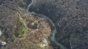 Top view on river in autumn. Clip. River surrounds yellow field and green forest. Mountains slopes covered with lush. Green vegetation in foreground stock video footage