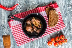 Top view roasted chicken giblets in pan and bread. Top view frying pan with delicious roasted chicken giblets with rye bread, tomatoes and wooden spatula on Stock Photo