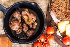 Top view roasted chicken giblets in pan and bread. Top view frying pan with delicious roasted chicken giblets with rye bread and tomatoes. Selective focus Royalty Free Stock Image