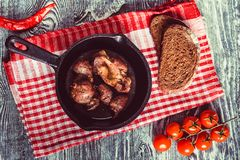 Top view roasted chicken giblets in pan and bread. Top view frying pan with delicious roasted chicken giblets with rye bread and tomatoes on checkered cloth Royalty Free Stock Image