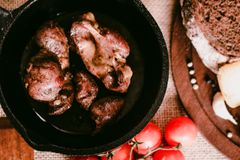 Top view roasted chicken giblets in pan and bread. Top view frying pan with delicious roasted chicken giblets with rye bread and tomatoes. Selective focus Stock Images