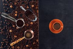 Roasted coffee beans, scoop, coffee pot, coffee tamper and cup of coffee on black royalty free stock photos