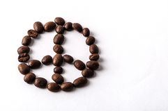 Coffee beans arranged as a peace sign  on white background with copyspace. Top view of roasted organic coffee beans as decorative concept of peace, fair trade or Royalty Free Stock Photography