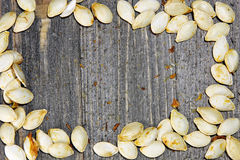 Top view of roasted pumpkin seeds on a wooden background Stock Image