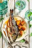 Roasted seabream and potatoes with cherry tomatoes. Top view of roasted seabream and potatoes with cherry tomatoes stock image