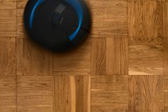 Robovac on on parquet floor. Top view of robotic vacuum cleaner on wooden parquet floor, natural movement, natural motion blur Stock Image