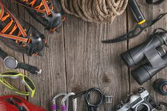 Top view of rock climbing equipment on wooden background. Chalk bag, rope, climbing shoes, belay/rappel device, carabiner and asce. Nder. Active lifestyle stock photography