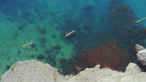 Top view from the rock of kayaks kayaking and enjoying the tropical crystal clear turquoise blue waters in paradise. Top View of Kayaks kayaking and enjoying the stock footage