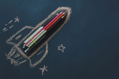 Top view rocket fling on the space with star. Crated by colorful pencil and drawing by chalk board on backboard or table.Start up business.Back to school and stock photos