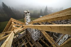 Top view of roof frame from wooden lumber beams and planks on walls made of hollow foam insulation blocks. Building, roofing,. Construction and renovation stock photo