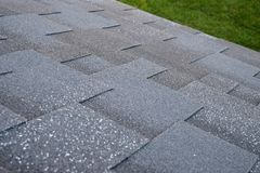 Top view of a roof made of asphalt shingles against a green lawn background. Royalty Free Stock Photos