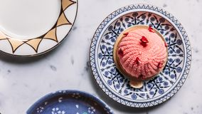 Top view of Rose and Lychee Mousses Cake decorated with rose petals in blue and white porcelain plate on marble background stock images