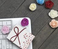Top view of roses, white laptop and gift box on background. stock photo
