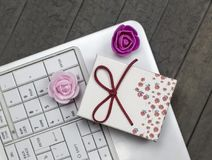 Top view of roses, white laptop and red gift box on background. royalty free stock photo