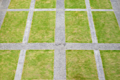 Top view of rough stone walkway with green grassy lawn Stock Photography