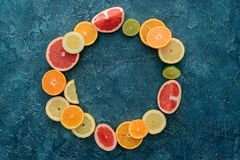 Top view of round frame made of citrus fruits slices on blue. Concrete surface royalty free stock photo