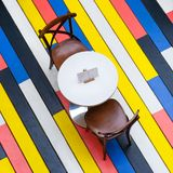 View on a round table and chairs on a multi-colored wooden floor in cafe square aspect ratio. Top view on a round table and chairs on a multi-colored wooden royalty free stock photography