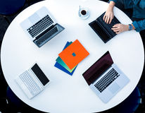 Top View of Rounded Desk with Four Laptops Stock Photo