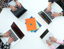 Top View of Rounded Desk with Four Laptops and People Hands Stock Photos