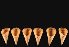 Top view of row of appetizing ice cream cones. Isolated on black royalty free stock photography