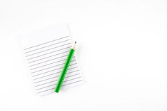 Top view of Ruled paper notepad with green pencil on white backg Stock Image